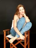 Schöne entspannte junge Frau, die in einem Stuhl sitzt Stockfoto