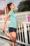 Schöne erfüllte junge Frau, die nach einem harten Training ausdehnt und stillsteht stockfotos