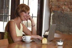 Schöne erfolgreiche Frau, die an der Kaffeestube mit der Laptop-Computer genießt Kaffeetasse arbeitet Lizenzfreie Stockbilder