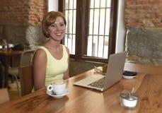 Schöne erfolgreiche Frau, die an der Kaffeestube mit der Laptop-Computer genießt Kaffeetasse arbeitet Stockfoto