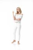 Schöne ernste blonde Frau in der weißen Bluse und in den Hosen auf weißem Hintergrund Stockbild