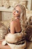 Schöne erstaunliche blonde Frau in der sexy Wäsche mit Pelzsitzen Lizenzfreie Stockbilder