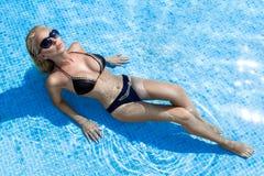 Schöne erstaunliche elegante sexy blonde vorbildliche Frau mit dem perfekten Gesichtstragen Sonnenbrille in einem Pool mit elegan Stockfoto