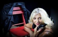 Schöne erwachsene blonde Frau, die auf dem Boden sitzt Lizenzfreies Stockfoto