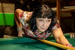 Schöne erwachsene Frau konzentriert das Zielen des Billardstocks auf das GR lizenzfreies stockfoto