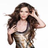 Schöne erwachsene Frau mit dem langen braunen gelockten Haar Stockfotos