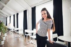 Schöne erwachsene Frau mit einem perfekten Lächeln, das in einem Café steht Stockfoto