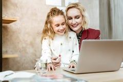 Schöne erwachsene Mutter mit dem breiten Lächeln, das ihre Tochter trägt lizenzfreie stockfotografie