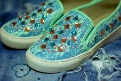 schöne Espadrilles mit Bergkristallen auf einem Hintergrund von Jeans lizenzfreies stockfoto