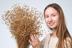Schöne europäische Frau mit langem Haarholdingblumenstrauß von trockenen Blumen des Flachses lizenzfreies stockbild