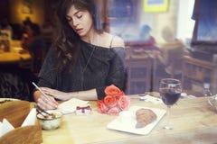Schöne europäische Frau mit langem Haarschreiben im Notizbuch nahe Fenster im Café Romantisches Frühstück, Datum oder St.-Valenti Lizenzfreie Stockfotografie