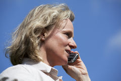 Schöne fällige blonde Frau mit Mobiltelefon Stockbild