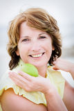Schöne fällige Frau, die einen Apfel anhält Stockfoto
