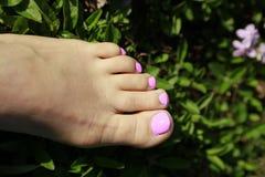 Schöne Füße, die am Badekurort im Freien sich entspannen Lizenzfreie Stockfotos
