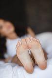 Schöne Füße, liegend im Bett einer jungen Frau lizenzfreies stockbild