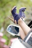 Schöne Fahrwerkbeinschuhe der Frauen, Autofenster stockfoto