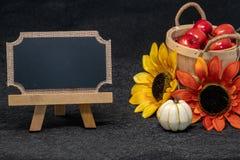 Schöne Fall- und Herbstszene mit einem Korb von Äpfeln, von bunten Sonnenblumen und von leerer Tafel lizenzfreie abbildung