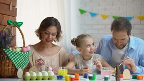 Schöne Familie, die Ostereier mit bunter Farbe, alte Traditionen verziert stock video