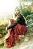 Schöne feenhafte Blondine gekleidet in einem roten Sitzen auf den roccks lizenzfreies stockfoto