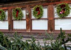 Schöne Feiertagskränze und -Tannenzweige auf hölzernem Gebäude Lizenzfreie Stockfotos