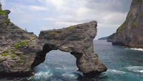 Schöne Felsen-Bogen-Insel im Meer an Atuh-Strand in Nusa Penida, Indonesien Antenne 4k stock video footage