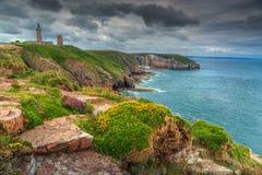 Schöne felsige Küstenlinie mit Leuchtturm an der berühmten Kappe Frehel, Frankreich lizenzfreies stockbild