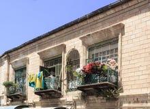 Schöne Fenster und Balkone, verziert mit Blumen Stockbild