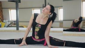 Schöne flexible Frau sitzen auf Schnur im Studio vor Spiegel stock video footage