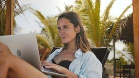 Schöne fokussierte kaukasische Workaholicgeschäftsfrau, die im Urlaub im beweglichen Büro des Laptops im exotischen Strandstuhl a stock footage
