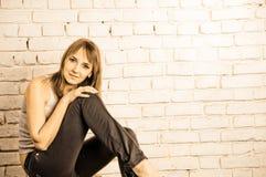 Schöne Frau auf Backsteinmauer Stockbild