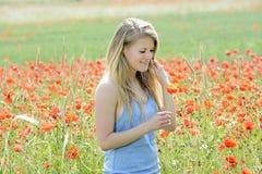 Schöne Frau auf dem Mohnblumegebiet Stockfotos