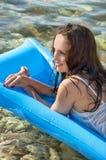 Schöne Frau auf einer Matratze auf dem Meer Stockbild