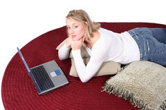 Schöne Frau auf Fußboden mit Laptop-Computer Stockfotos