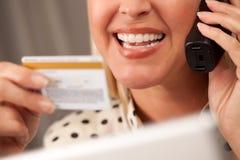 Schöne Frau auf Telefon-Holding-Kreditkarte lizenzfreie stockbilder