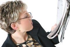 Schöne Frau in den dreißiger Jahren Zeitung über Weiß lesend lizenzfreie stockfotografie
