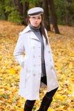 Schöne Frau in der Schutzkappe und im weißen Mantel Stockfotografie