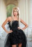 Schöne Frau in der schwarzen Kleideraufstellung im Freien Lizenzfreie Stockfotografie