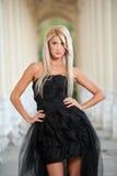 Schöne Frau in der schwarzen Kleideraufstellung im Freien Stockfotos