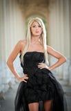 Schöne Frau in der schwarzen Kleideraufstellung im Freien Stockbild