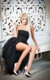 Schöne Frau in der schwarzen Kleideraufstellung im Freien Stockfoto
