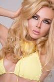 Schöne Frau des blonden Haares in der sexy gelben Wäsche mit Kopfhörern Lizenzfreie Stockfotografie