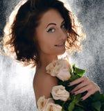 Schöne Frau des gelockten Haares mit Blumenstrauß von wilden Rosen blüht wi Stockfoto