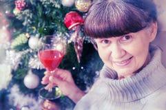 Schöne Frau des reifen Alters gegen Weihnachtsbaum Abstraktes Hintergrundmuster der weißen Sterne auf dunkelroter Auslegung Lizenzfreie Stockfotos