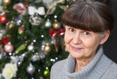 Schöne Frau des reifen Alters gegen Weihnachtsbaum Abstraktes Hintergrundmuster der weißen Sterne auf dunkelroter Auslegung Stockfoto