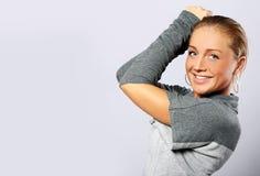 Schöne Frau, die über grauem Hintergrund aufwirft Stockfoto
