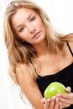 Schöne Frau, die auf Bett sitzt und Apfel anhält Stockfoto