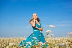 Schöne Frau, die auf Blumenfeld geht Lizenzfreie Stockbilder