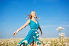 Schöne Frau, die auf Blumenfeld geht Lizenzfreie Stockfotos