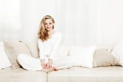 Schöne Frau, die auf Couch sitzt Lizenzfreie Stockbilder