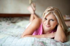 Schöne Frau, die auf das Bett legt Lizenzfreie Stockfotografie